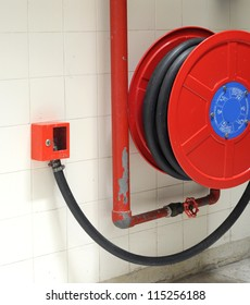 red fire hydrant reel on a wall