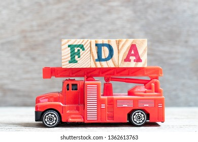 Red fire truck hold letter block in word FDA (abbreviation of food and drug administration) on wood background
