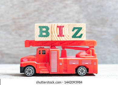 Red fire truck hold letter block in word biz (abbreviation of business) on wood background