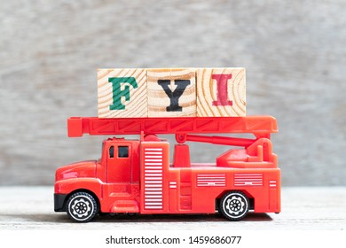 Red fire truck hold letter block in word FYI (Abbreviation of For your information) on wood background