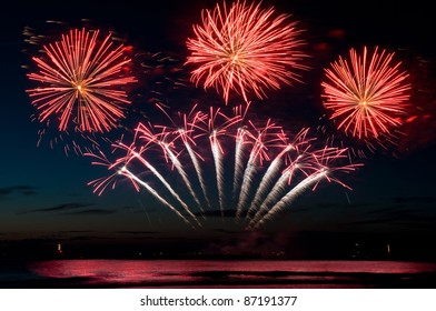 red firework explosions above the sea