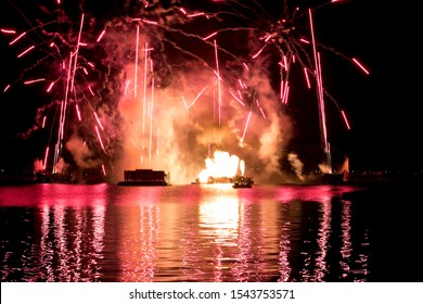 Red fireworks reflections in water