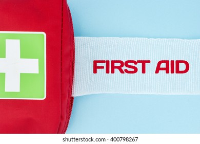 Red first aid kit with unrolled gauze with First Aid text, on light blue background.