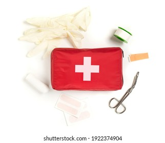 Red first aid medical kit bag with scissors, tape and gloves top view flat lay from above over white background