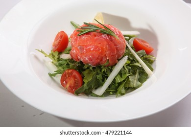 Red fish on Arugula on plate with tomatoes