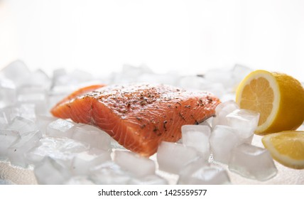 Red fish on the background of ice and lemon halves. Still life with a piece of salmon on ice and lemon