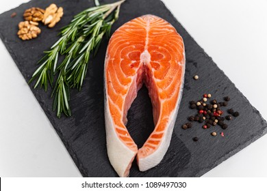 Red fish on the black stone board with ingredients, salmon, top view
