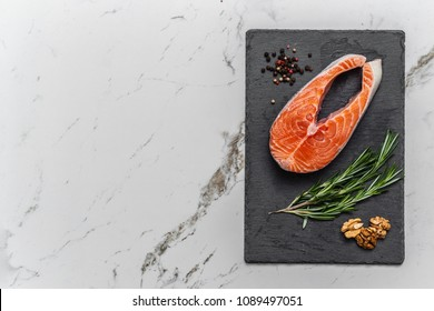 Red fish on the black stone board with ingredients, salmon, top view, place for text