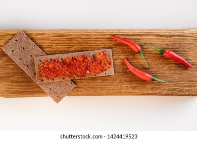 red fish roe on ryea loaf of bread and three chili peppers