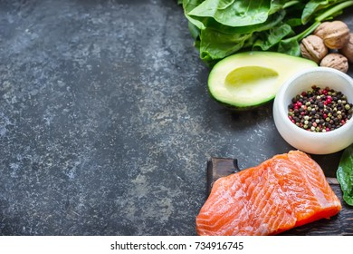 Red fish with spices, greens and avocado on grey stone background. Selective focus. Top view.