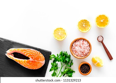 Red fish with spices. Salmon steak on cutting board near sea salt, pepper, lemon slices, greenery on white background top view space for text