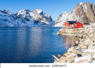 Red Fisherman house in front of a snow covered mountain range on Lofoten islands in winter
