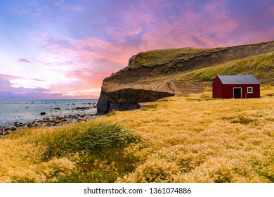 Red fisherman's cottage near the coast in the small village Cameron. Sunset time. Tierra del Fuego, Chile