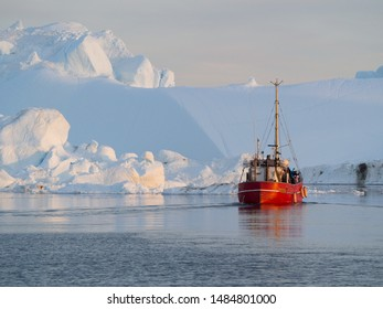 A red fishing boat motors through tranquil sea surrounded by icebergs.Greenland.Arctic - Image