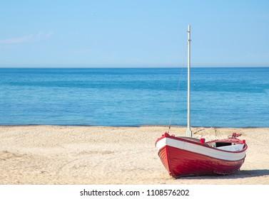Red fishing boat on the beach at Vorupor village Jutland, Denmark. Danish landscape with blue sky background
