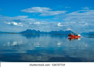 Red fishing boat sailing on water with mountains in distance near Svolvaer in Norway.