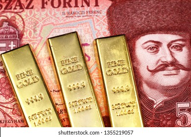 A red five hundred Hungarian forint bank note close up in macro with three gold bars