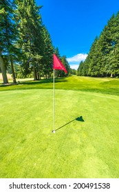 Red flag at the beautiful golf course in a sunny day. Canada, Vancouver. Vertical.