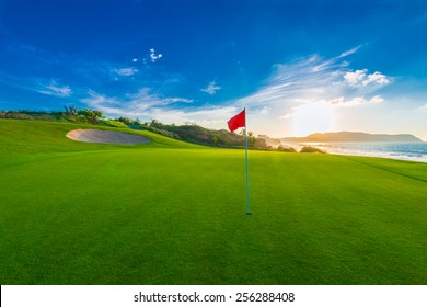 Red flag at the beautiful golf course at the ocean side at sunset, sunrise time.
