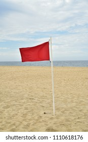 red flag flying on flag pole on beach