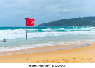 Red flag no swimming here sign at beach in windy day.