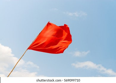 Red flag on the beach, on the background of blue sky. Warning about the dangers