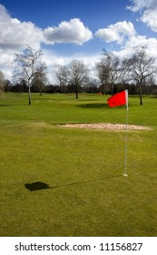 Red flag on the putting green of a golf course on a sunny winter day