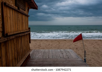 Red flag on the stormy beach