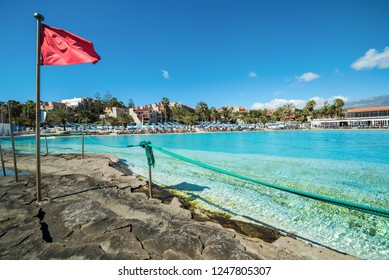 Red flag on tropical swimming pool
