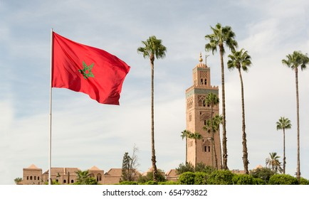 Red flag with palms from Morocco and Djemma el Fna tower. Touristic place in Marrakesh used by local people as square or market place. Emblematic landscape - traditional building from arabic culture.