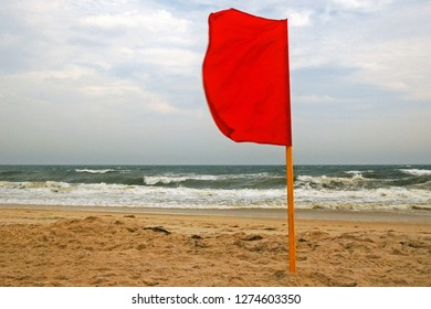 A red flag is planted in the sand, forbidding swimming due to rough waters