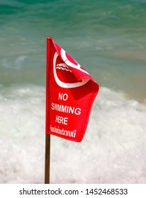 "Red flag with the sign ""No swimming"" on the beach on background of big storm waves. Red lifeguard flag on Nai Harn Beach, Thailand"