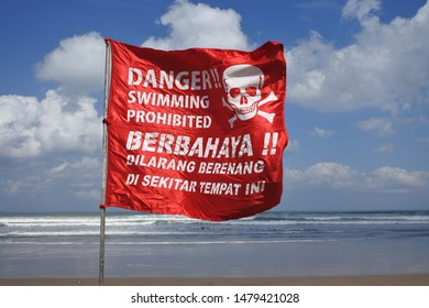 Red flag with skull sign reading Danger swimming prohibited on a beach in Bali Indonesia.