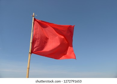 red flag swaying in the wind on a blue sky background.