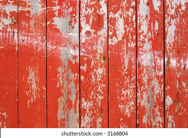 Red flaky paint on a wooden fence.