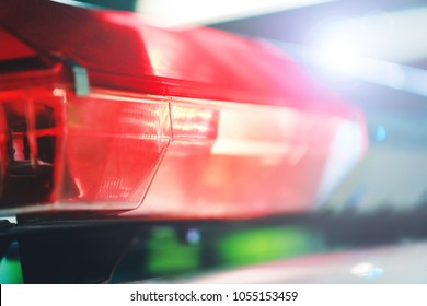 Red flasher on the police car at night. Red light flasher of a police car. Siren on police car flashing. Police red light and siren on the car in the street.