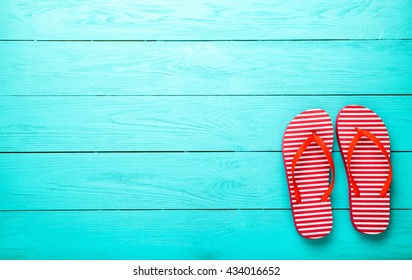 Red flip flops on blue wooden floor. Top view and copy space