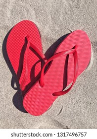 Red flip flops on the sand in the shape of a heart