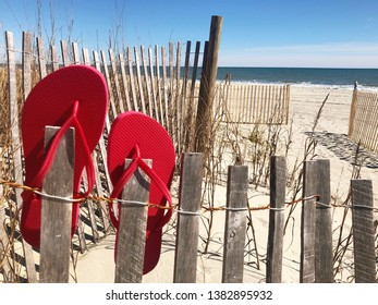 Red flip flops on a weathered wooden beach fence with Atlantic Ocean in background.