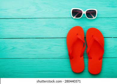 Red flip flops and sunglasses on blue wooden background
