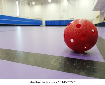 Red floorball ball on floorball court