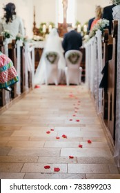 red flower petals on a church floor during a wedding ceremony