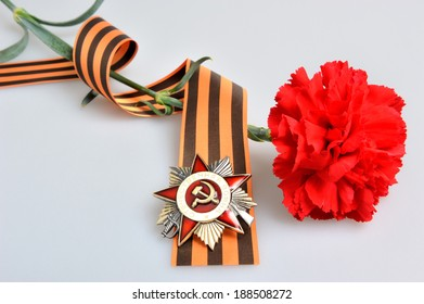 Red flower tied with Saint George ribbon and order of Great patriotic war on gray