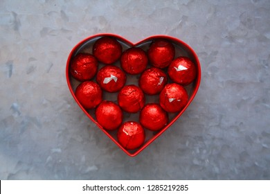 red foil wrapped Chocolate balls inside a  red heart metal shape. On  silver metal background.