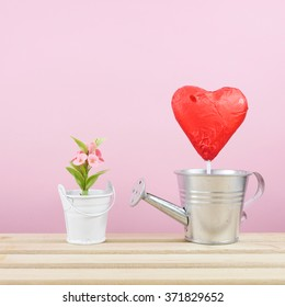 The red foiled chocolate heart stick with small silver watering can and mini fake flower in small bucket on wooden tray for Valentine's day.