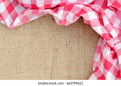 Red folded checkered rural tablecloth over canvas shaped like frame