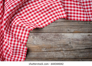 Red folded tablecloth on an old wooden table. Close up