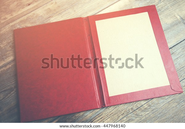 A red folder on wooden table