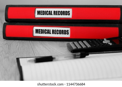 Red folders with medical records written on the label on a desk with selective colour