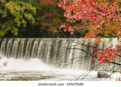 Red foliage in Blackstone Gorge with waterfall in background